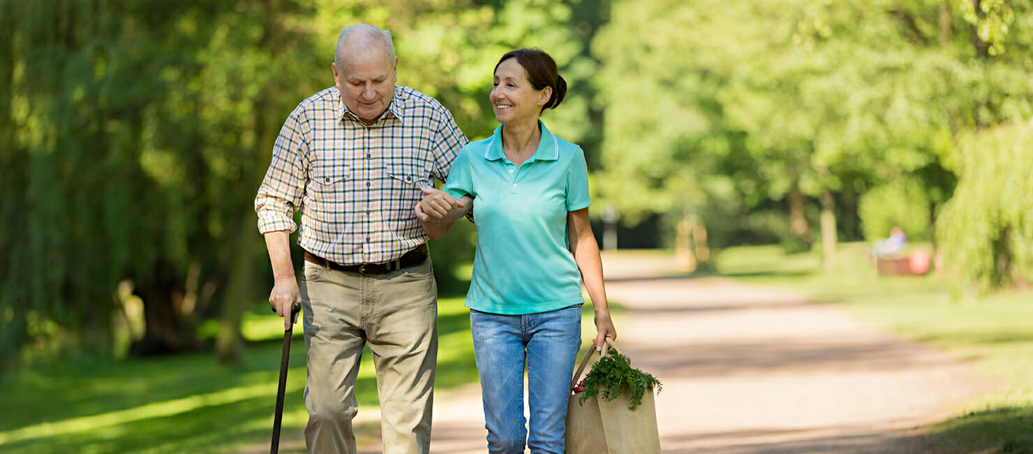 Elderly man walking wiht care aid bringing home groceries