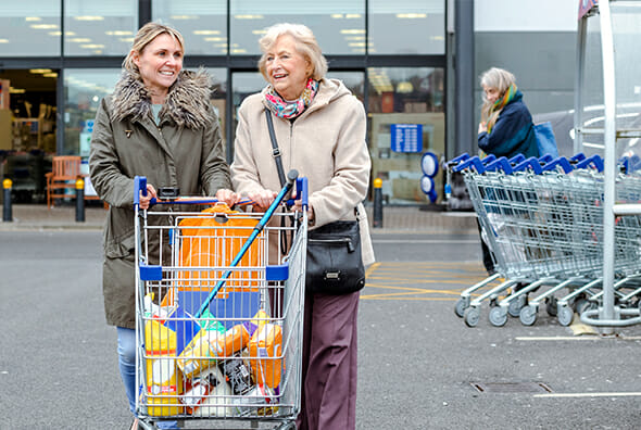 Elderly woman and care aid pushing shopping cart in parking lot
