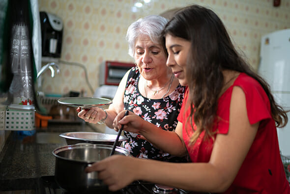 Care aid and older woman cooking