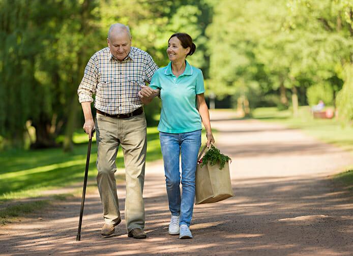 Elderly man walking wiht care aid bringing home groceries
