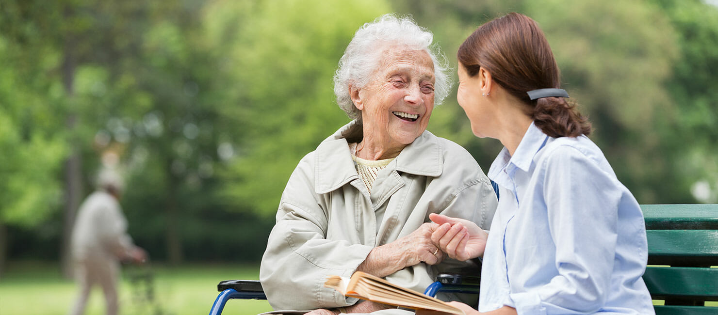 older woman sitting in wheelchair smiling and holding hands with younger woman sitting on bench with open book